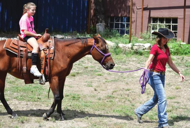 Elizabeth Earheart guides Coraline Warman, age 10, in a horseback riding pen set up for SeptemberFest events. The space was behind the Tres Molinos business on the main road in Harper.