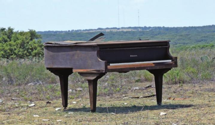 A Schumann piano was placed in the middle of a pasture on Ranch Road 965 over the summer by Albert Holzscheiter. Since then, the classical instrument has garnered attention from locals and tourists. — Standard-Radio Post/Samuel Sutton