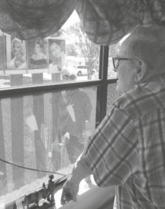 James Cooper looks out the window from his room at the Knopp Assisted Living Center to see a photo board created by his two daughters and son-in-law to help him celebrate his 89th birthday on April 27. — Submitted photo