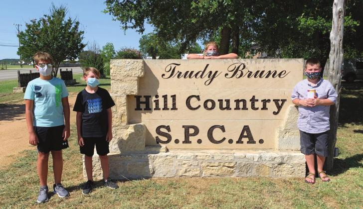 Making their donation to the Hill Country SPCA, from left, Kaden Montgomery, John Lutz, Ross DiCuffa and Nathan Benfield have been collecting donations for the past three months during the COVID-19 pandemic. — Submitted photo