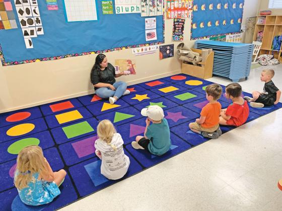 Ariana Cisneros, a teacher at Bethany Preschool, reads to students by practicing social distancing. Many area child care facilities are updating and changing their policies and procedures due to COVID- 19 and the start of the new school year. — Standard-Radio Post file photo