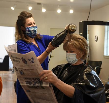 Hair stylist Jamie Laratta, left, styles Teri Ewing's hair on Friday, the first day salons have been open since March 18. With the opening, salons are required to follow new procedures from stylists and clients wearing masks to extra cleaning. — Standard-Radio Post/McKenzie Moellering