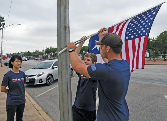 Admin Officer Kathy Karr, left, observes Commanding Officer Matthew Willingham and Chaplain Matthew Grobe as they hang the American and Texas flags in front of the Gillespie County Courthouse. Fredericksburg High School Navy Junior Reserve Officers' Training Corps (NJROTC) program students place these flags 10 times a year in front of businesses who request this service. — Standard-Radio Post/Samuel Sutton