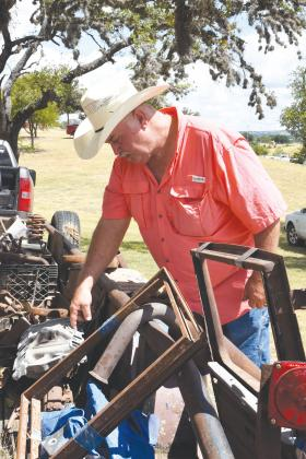 Ronnie Stanley of Burton sifts through old auto parts at the 43rd Hill Country Auto Swap Meet. The Swap Meet included booths and trailers with auto parts for sale.