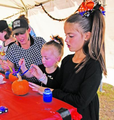 Kristy Tinney, of Mason, paints on a pumpkin with her daughters Parker, 2, and To-ryn, 8, during Bestfest at Marktplatz on Saturday, Oct. 15. The annual event is sponsored by the Knights of Columbus Council 9765 and proceeds from Bestfest are used to sponsor local organ-izations. — Standard-Radio Post/Scott Allen