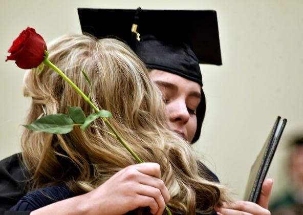 New Heritage School graduate Celia Ashley hugs her mother (and teacher at the school) Wendy Ashley during Friday commencement ceremonies held in the school gymnasium. See story and more photos on page C/D1. — Standard-Radio Post/Ken Esten Cooke